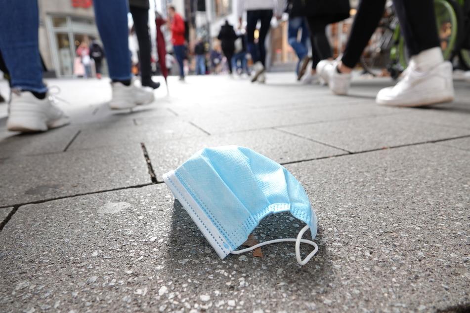 In der Kölner Fußgängerzone liegt eine Schutzmaske auf dem Boden. Zahlreiche NRW-Städte gelten neuerdings als Corona-Risikogebiete.