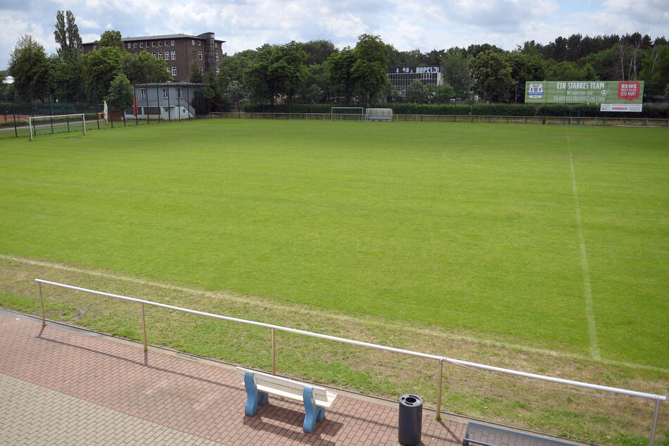 Blick über einen menschenleeren Rasenfußballplatz.