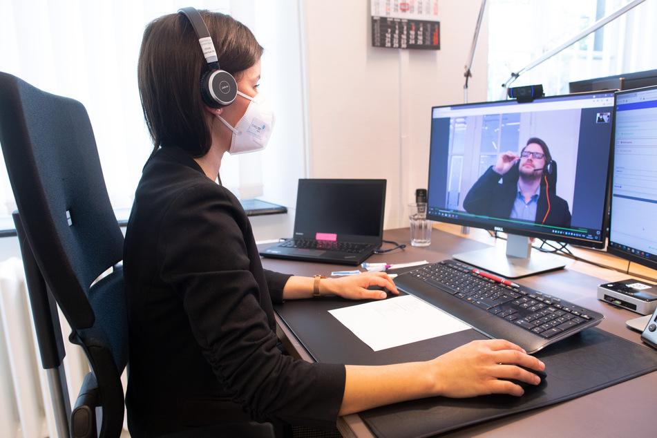 Eine Mitarbeiterin des digitalen Corona-Testzentrums kontrolliert den Test eines Patienten am Computer.