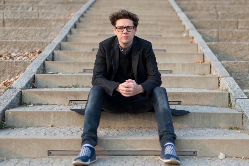 Schauspieler Christian Friedel sitzt auf einer Treppe am Dresdner Königsufer.