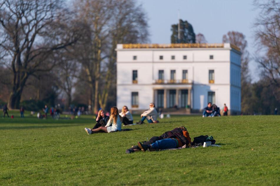 Menschen genießen das sonnige Wetter auf einer Wiese im Jenischpark.