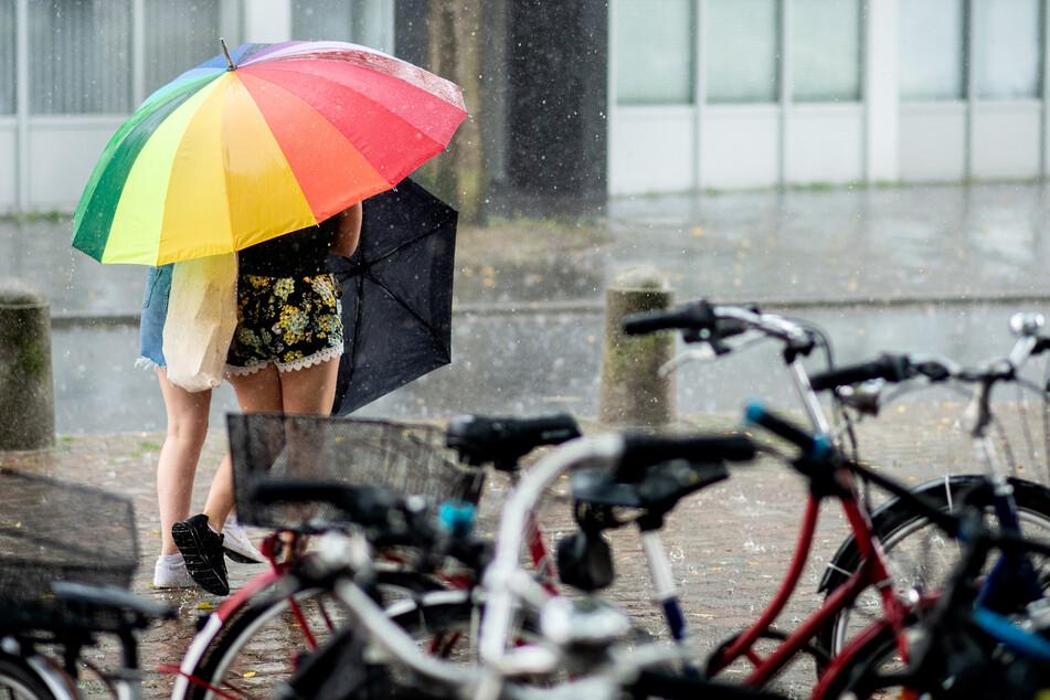 Zwei Frauen suchen unter einem bunten Schirm Schutz vor dem Regen.
