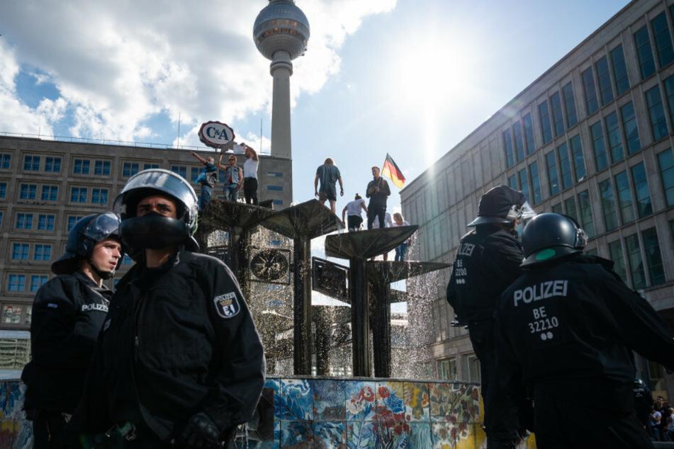 """Menschen sind bei einer Demonstration auf dem Alexanderplatz auf den Springbrunnen """"Brunnen der Völkerfreundschaft"""" geklettert."""