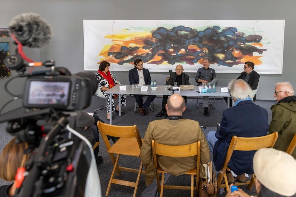 Max Uhlig (2.v.l.) bei der Pressekonferenz zur Ausstellungseröffnung in der Galerie Weise. Im Hintergrund ist ein Entwurf der Torgauer Aquarelle zu sehen.