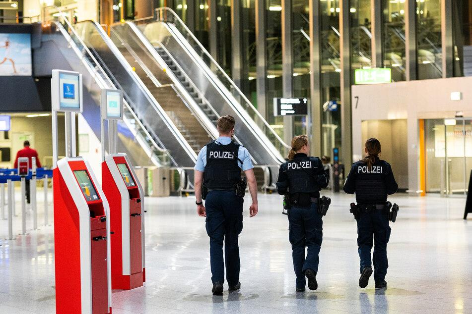 Drei Polizisten gehen durch das Terminal 1 am Flughafen in Frankfurt/Main.