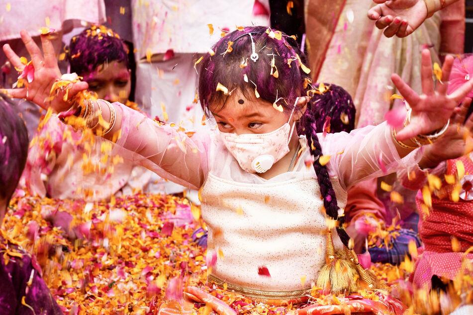 Ein Kind mit Mundschutzmaske sitzt während der Holi-Feierlichkeiten der Trishala-Stiftung inPrayagraj, Indien, inmitten von Blüten.