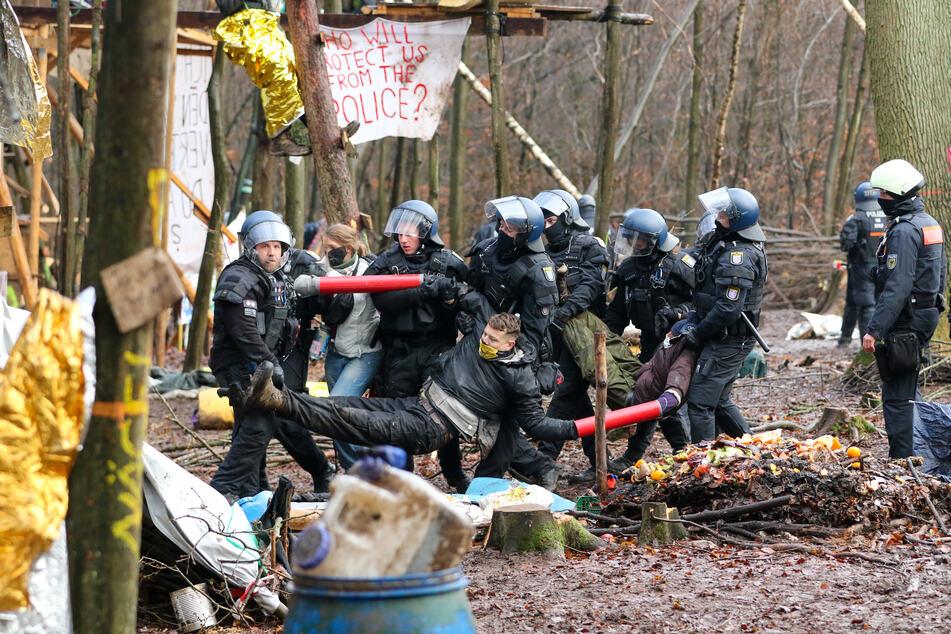 Polizisten tragen drei Aktivisten aus dem letzten verbliebenen Camp im Dannenröder Forst.