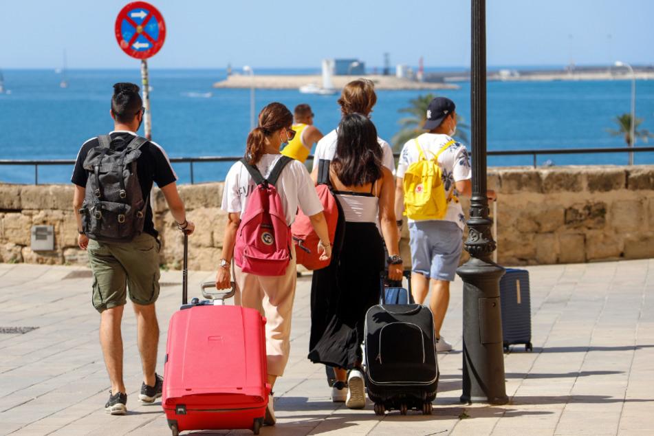 Spanien, Palma: Touristen gehen mit ihren Rollkoffern durch die Stadt.
