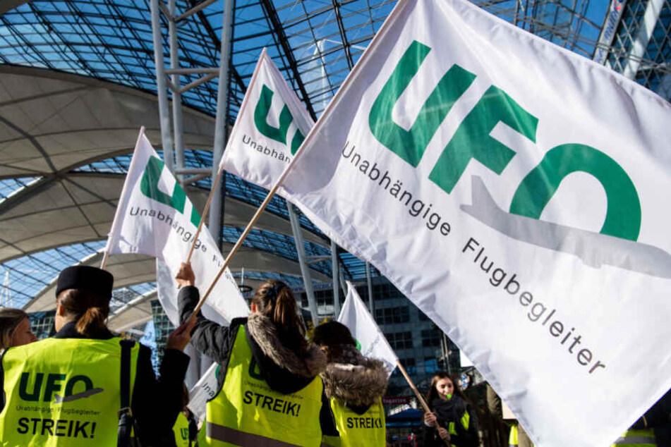 Streikende schwingen am 7.11.2019 am Flughafen München die Gewerkschaftsfahne.