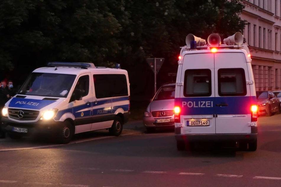 Rund um die Wurzner Straße sind zahlreiche Einsatzkräfte der Polizei unterwegs, die per Lautsprecher zum Anmelden der Versammlung aufrufen.