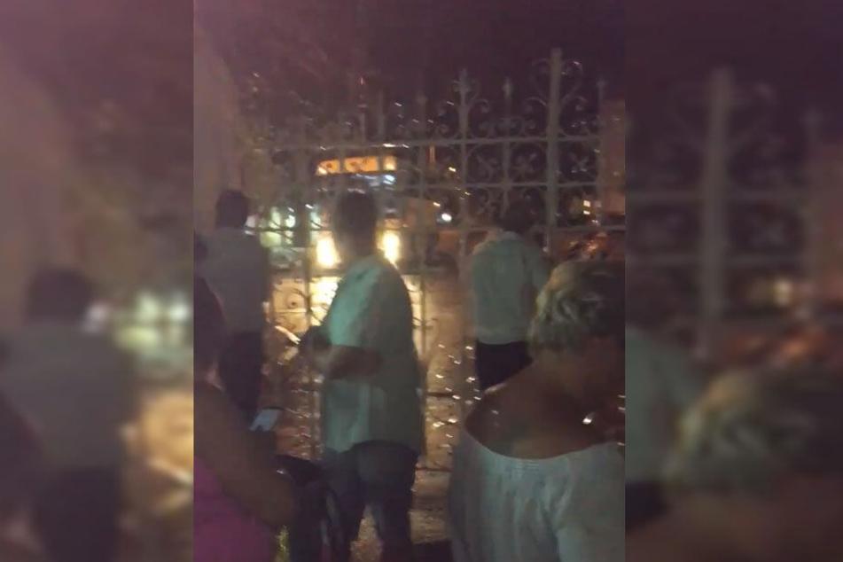 Touristen diskutieren vor dem geschlossenen Tor mit den Sicherheitsleuten.