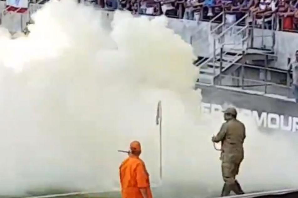 Der Feuerwehrmann versuchte mit seinem Feuerlöscher die Bienen zu vertreiben. Jedoch hüllte er lediglich weite Teile des Rasens in Nebel.