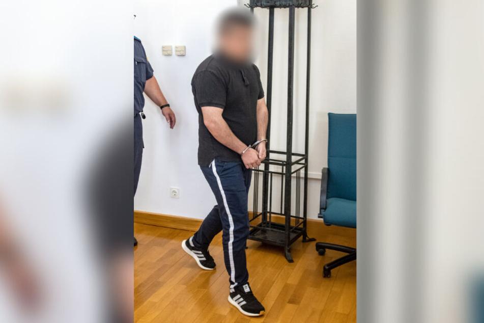 Der Angeklagte kommt in Handschellen in den Verhandlungssaal des Landgerichts.