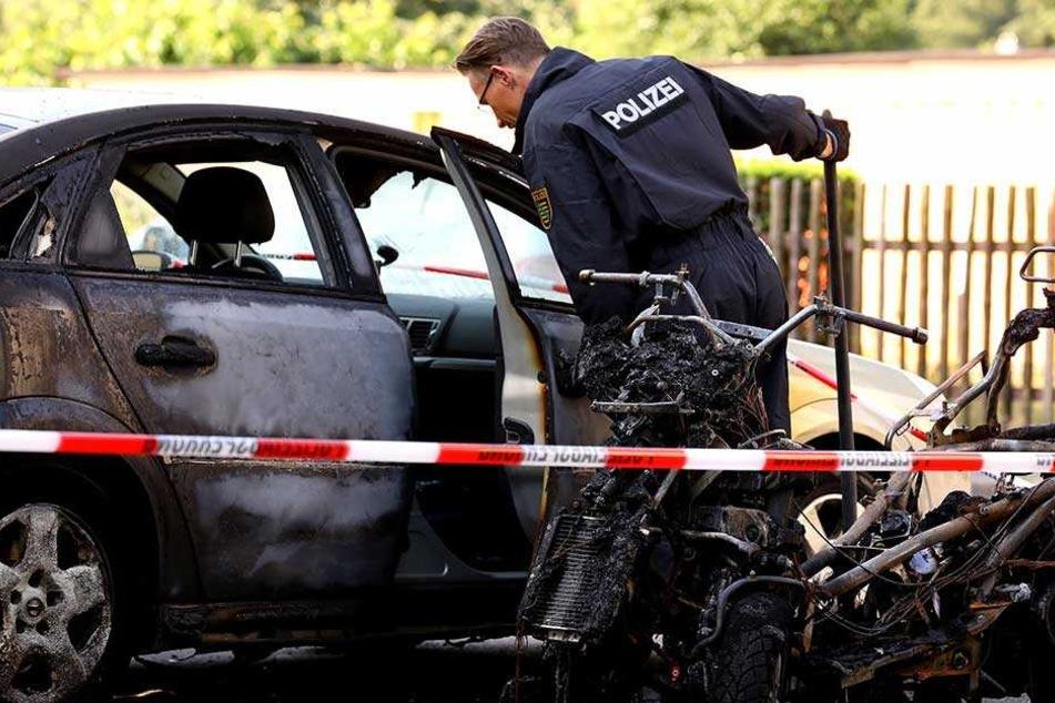Ein Polizist steht an den ausgebrannten Fahrzeugen in Prohlis.