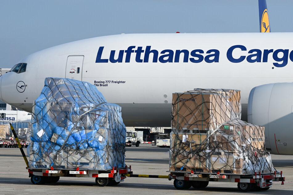 Eine Boeing 777 der Lufthansa Cargo rollt nach der Landung auf dem Vorfeld des Frankfurter Flughafens an Frachtgut vorbei.