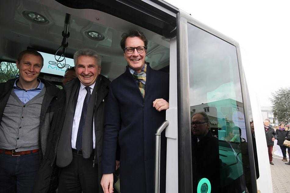 NRW-Wissenschaftsminister Andreas Pinkwart (m) und VerkehrsministerHendrik Wüst (r) stehen neben monheims Bürgermeister Daniel Zimmermann in einem autonom fahrenden Bus.