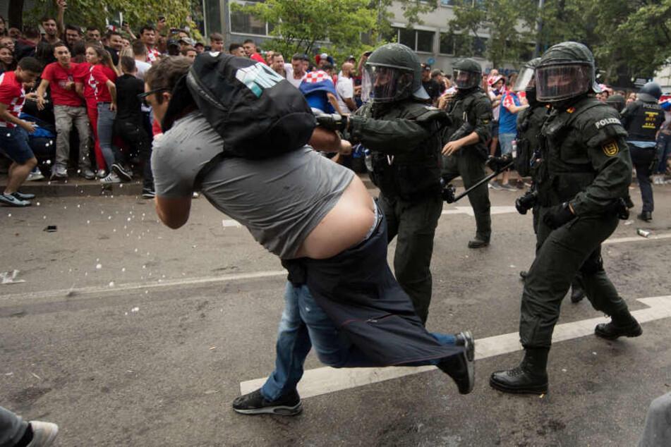Polizisten drängen auf der Theodor-Heuss-Straße einen Mann ab.