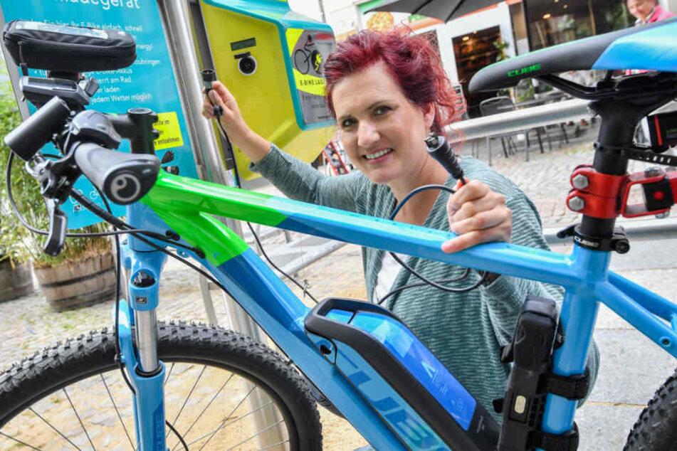 Erfolgreiche Premiere: Melanie Günther (35) von der Firma Göbau aus Wilkau-Haßlau nimmt auf dem Hauptmarkt die erste Zwickauer Ladesäule für E-Bikes in Betrieb.