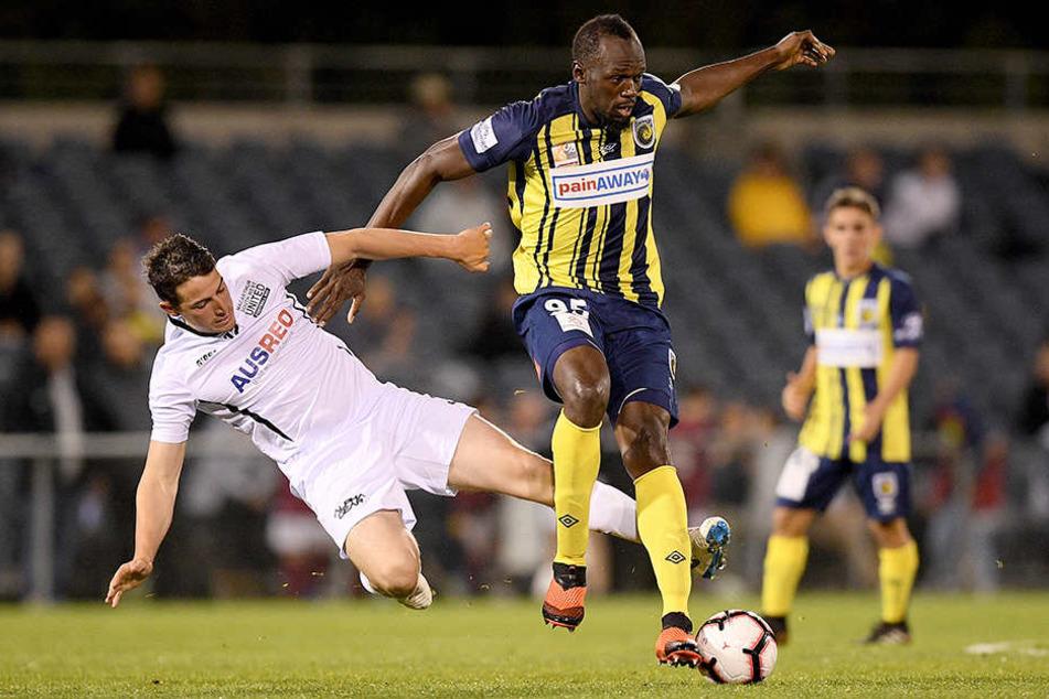 Usain Bolt (r.) behauptet sich im Zweikampf gegen Josh Symons von Macarthur South West United.