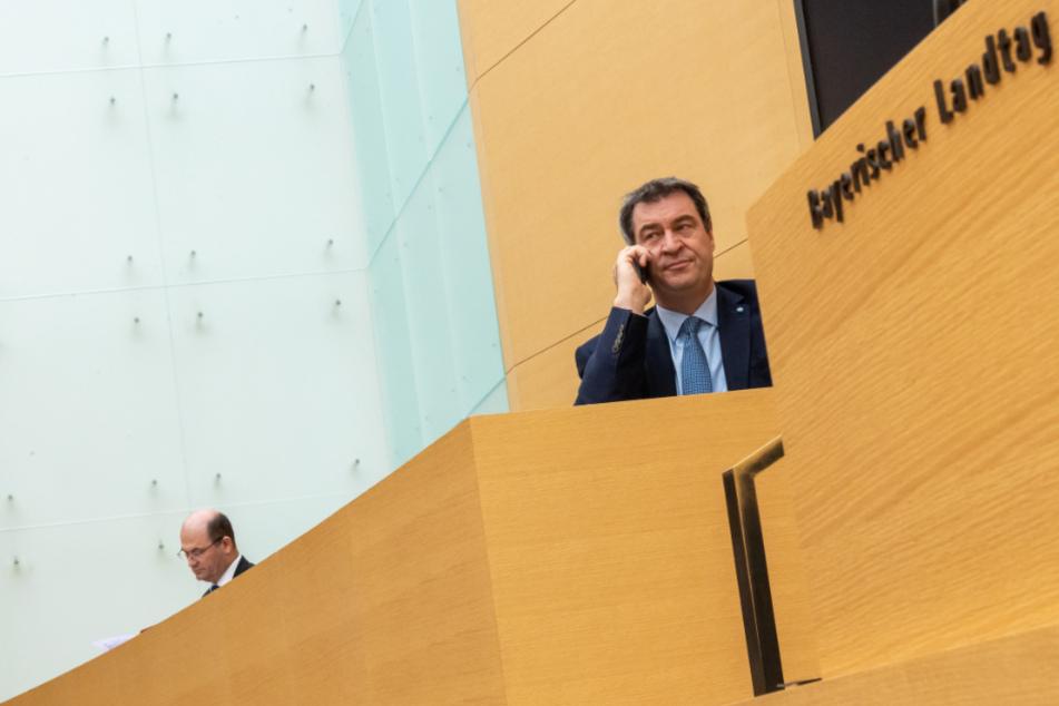 Markus Söder (r, CSU), Ministerpräsident von Bayern, telefoniert vor Beginn der Sitzung des bayerischen Landtags neben Albert Füracker (CSU), Staatsminister der Finanzen, Landentwicklung und Heimat.