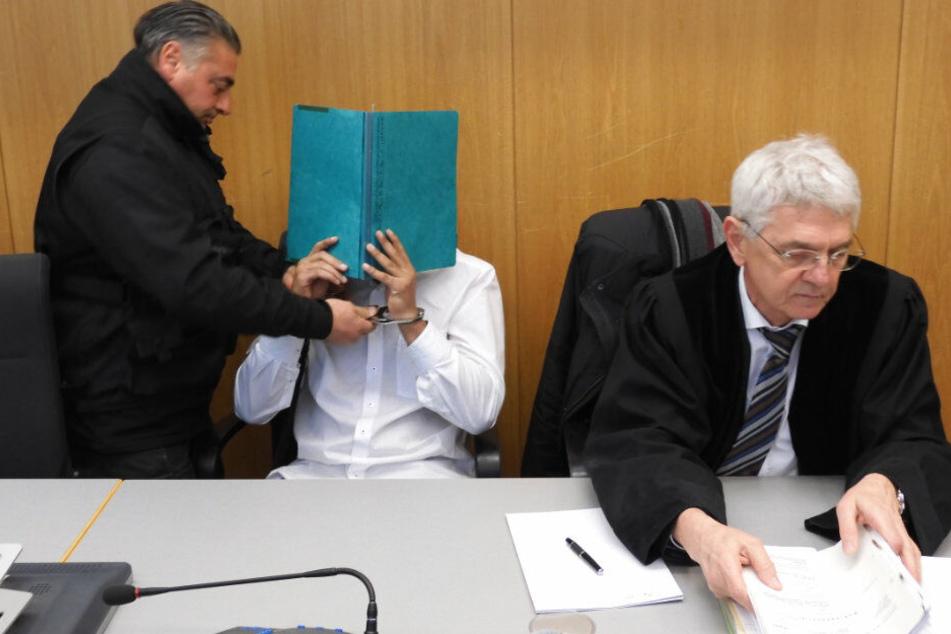 Ein Justizbeamter nimmt im Gerichtssaal dem Angeklagten die Handfesseln ab.