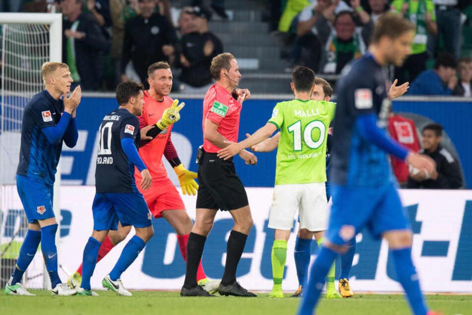 Die Braunschweiger Spieler sind außer sich nach dem unberechtigten Handelfmeter für Wolfsburg.