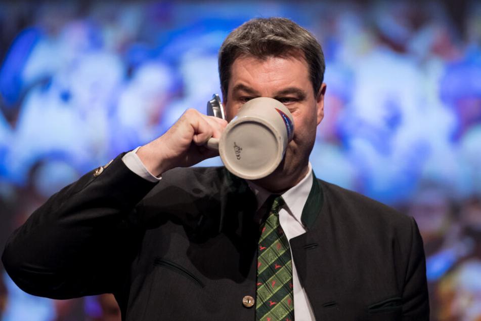 Markus Söder (CSU), damaliger Finanzminister von Bayern und amtierender Ministerpräsident, trinkt beim politischen Aschermittwoch der CSU nach seiner Rede ein Bier auf der Bühne. (Archivbild)