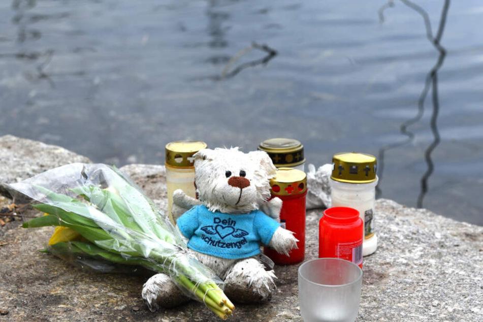 Blumen, Kerzen und ein Plüschtier liegen an dem Weiher in der Nähe des Fundortes der Babyleiche. (Archivbild)