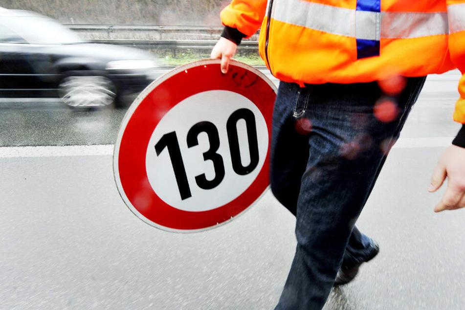 Ein Mitarbeiter der Autobahnmeisterei trägt auf der Autobahn 661 bei Frankfurt ein Schild zur Höchstgeschwindigkeit von 130 Stundenkilometern.