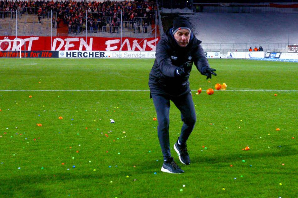 Zwickaus Mannschaftsleiter Mario Kallisch entsorgt die von Eintracht-Anhängern aufs Feld geworfenen Mandarinen.