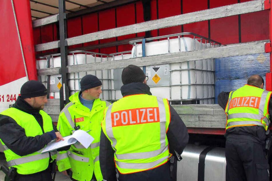 Beamte kontrollieren einen Gefahrgut-Laster.