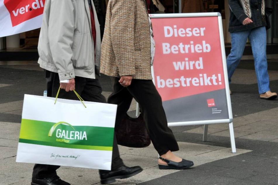 Ein Kunde mit einer Galeria-Kaufhof-Tüte geht an einem bestreikten Betrieb vorbei. (Archivbild)