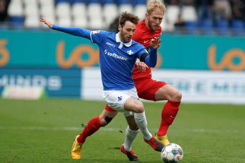 Darmstadts Matthias Bader (l) und Heidenheims Sebastian Griesbeck kämpfen um den Ball: Die Lilien hatten das Geschehen in der ersten Halbzeit vollkommen im Griff.