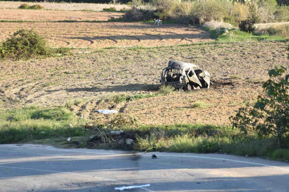 Das explodierte Wrack des Autos der populären Bloggerin Daphne Caruana Galizia auf einem Acker neben der Straße in Mosta.
