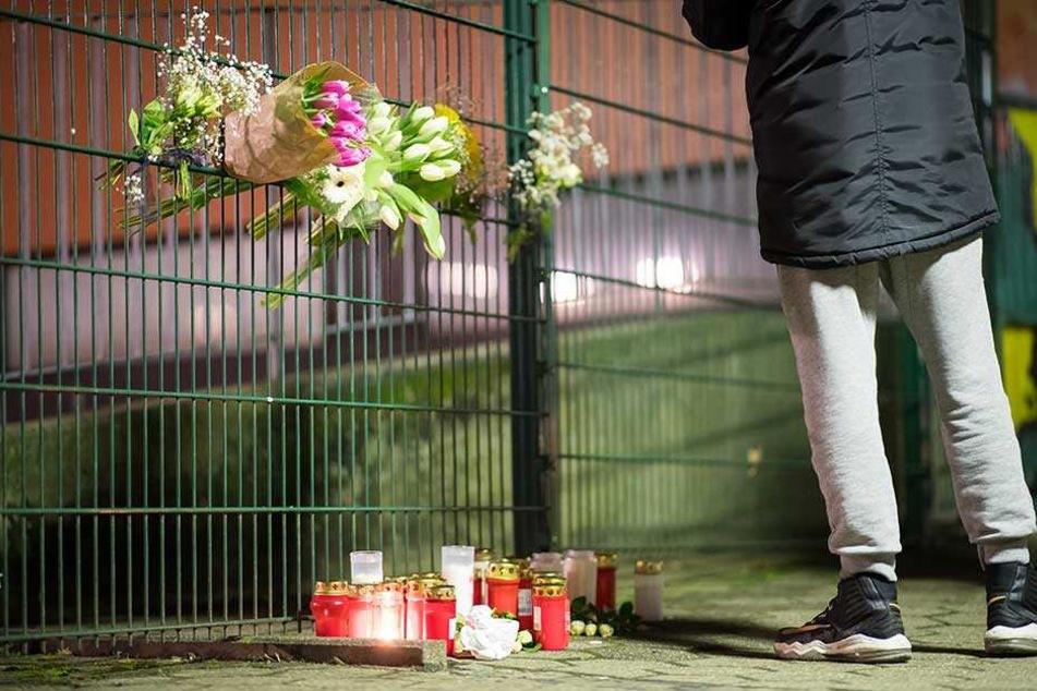 Trauernde haben Kerzen und Blumen am Zaun der Schule abgelegt.