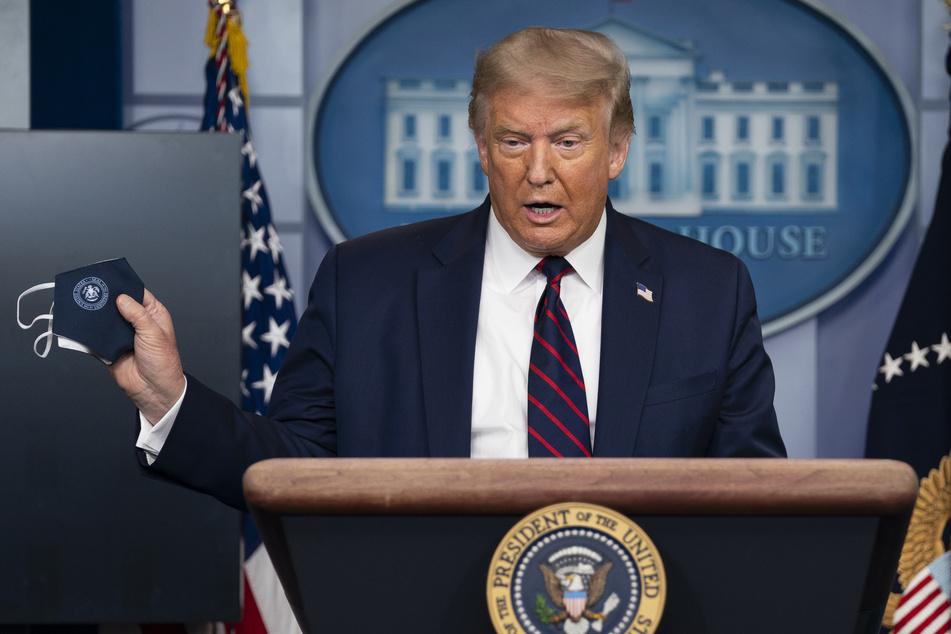 Donald Trump, Präsident der USA, hält auf einer Pressekonferenz im Weißen Haus eine Schutzmaske.