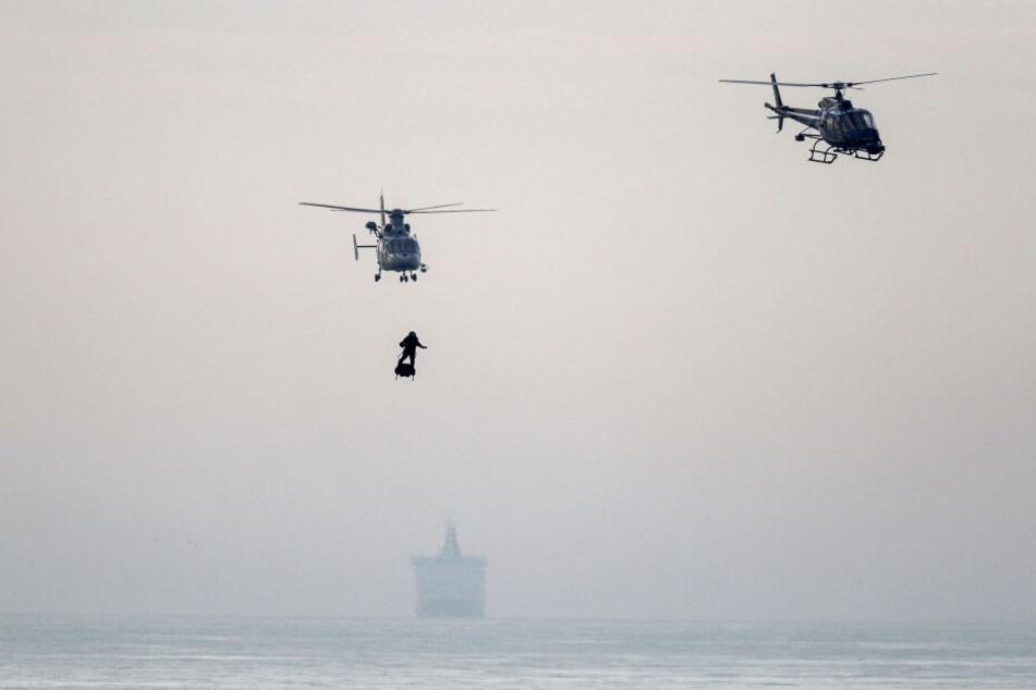"""Frankreichs """"Raketenmann"""" Franky Zapata ist begleitet von zwei Hubschraubern auf seinem Flyboard im Anflug auf den Strand von St. Margaret's, nachdem er den Ärmelkanal überquert hat."""
