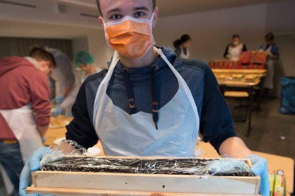 Ein Schüler zeigt einen weiteren Baustein für den Rekordkuchen.