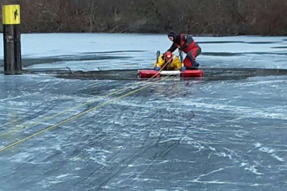 Feuerwehrmänner suchen im eisigen See nach einem untergegangenen Mensch. (Symbolbild)