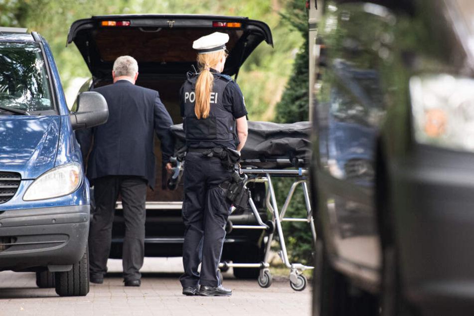 Die Leiche wird in den Wagen eines Bestatters verladen.