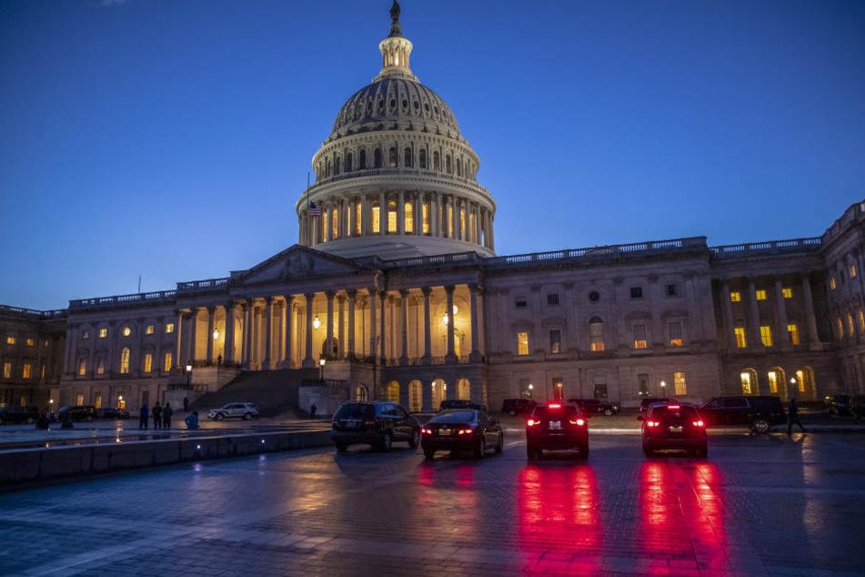 """Autos stehen in der """"blauen Stunde"""" vor dem Kapitol."""