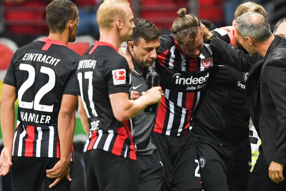 Frankfurts Cheftrainer Adi Hütter (r.), Timothy Chandler (l) und Sebastian Rode (2.v.l.) stehen beim verletzten Marco Russ (M).