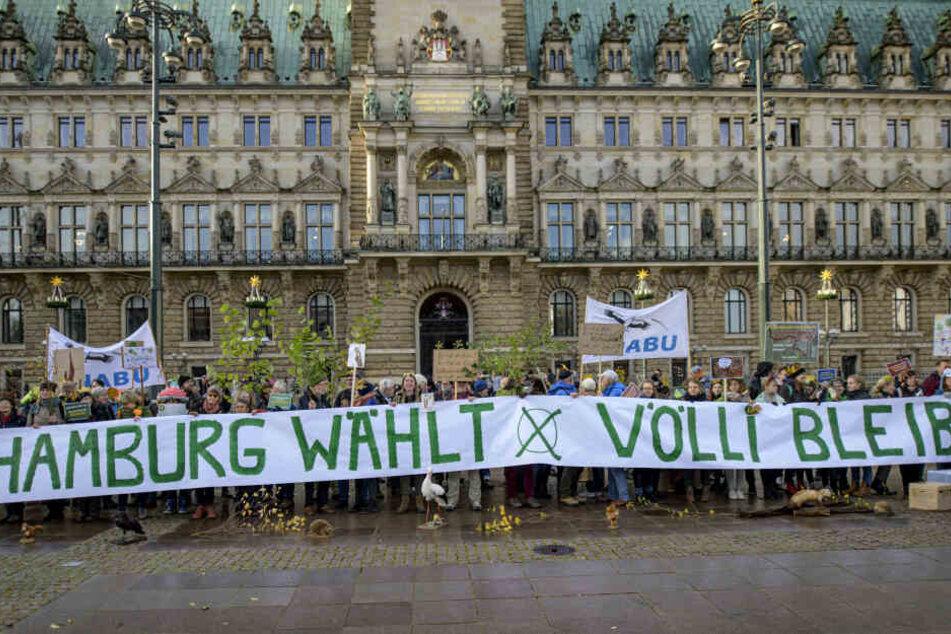 Teilnehmer einer Nabu-Aktion zum Erhalt des Vollhöfner Waldes protestieren vor dem Rathaus.