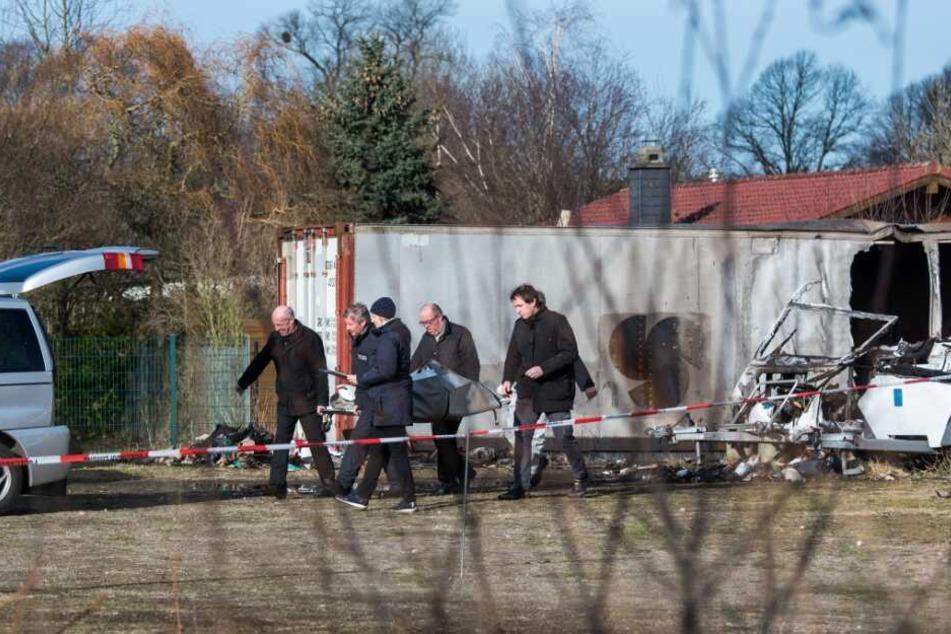 Ermittler der Polizei und Bestatter transportieren eine der Leichen ab.