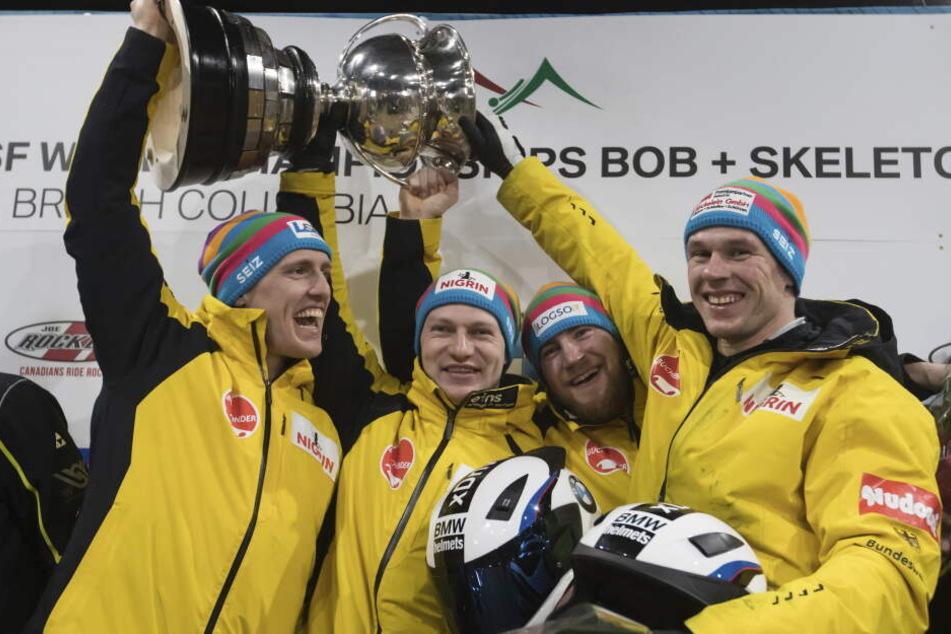 Thorsten Margis (l-r), Francesco Friedrich, Martin Grothkopp und Candy Bauer aus Deutschland halten die Trophäe.
