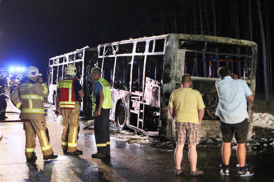 Ratlos stehen die beiden Männer (Fahrer und Beifahrer) vor dem ausgebrannten Linienbus.