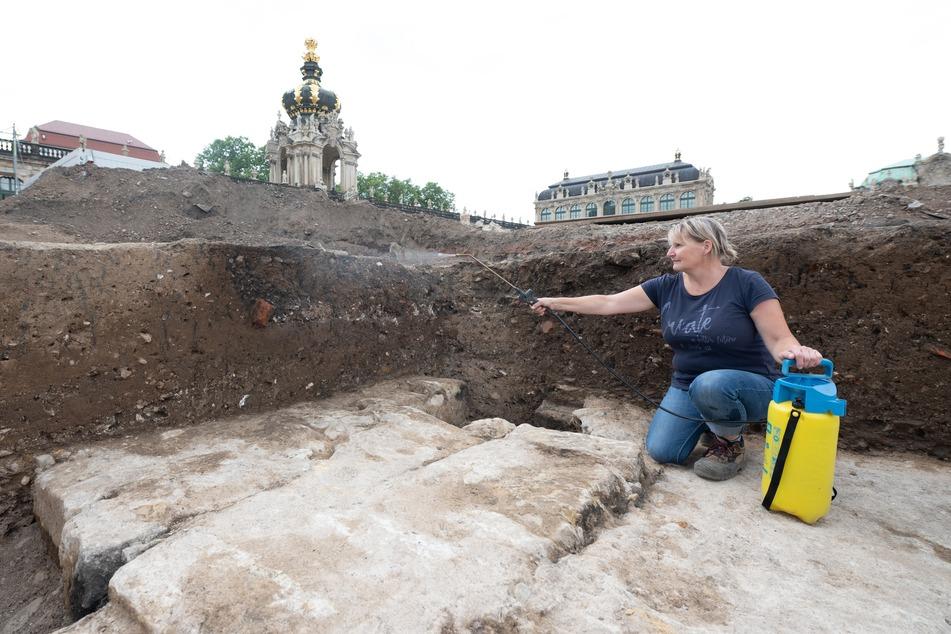 """Grabungsarbeiterin Katrin Ruffani bei Arbeiten im Zwingerhof. Sie hockt dabei auf dem her """"zufällig"""" freigelegten Fundament der Zwingergrotte."""