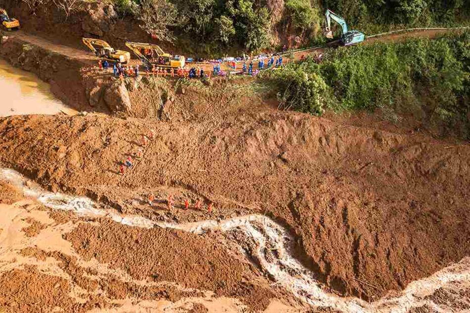 Das Luftbild zeigt Rettungshelfer, die an der Stelle des Erdrutsches nach Überlebenden suchen.
