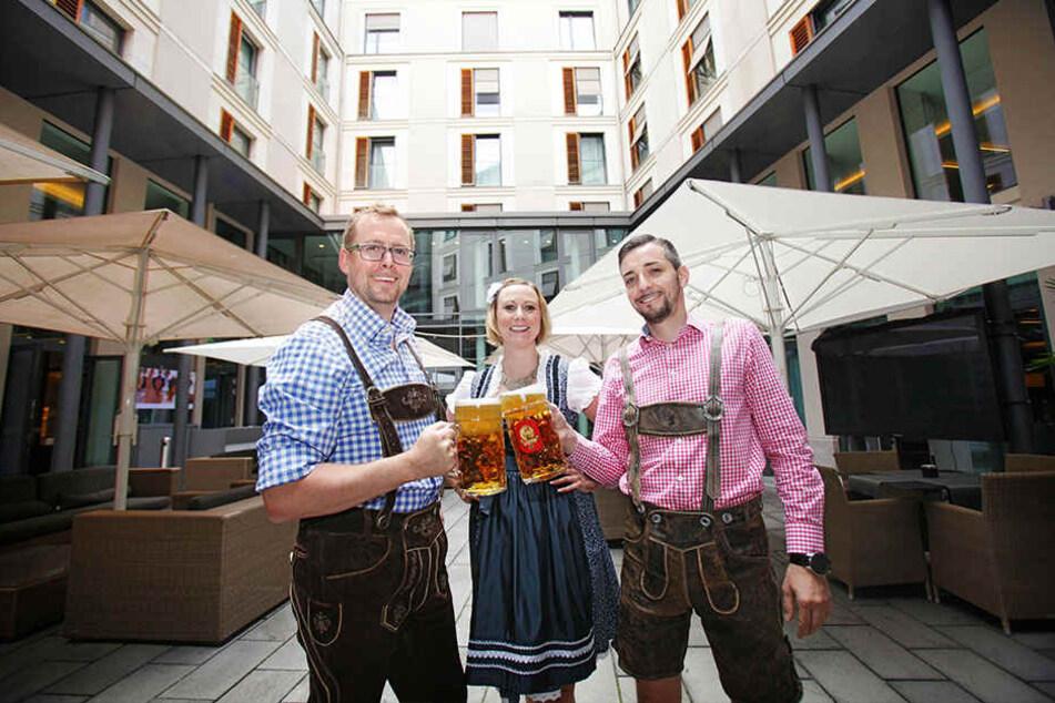 Die Innside-Hotelmitarbeiter Robert Straboth (41), Katharina Mohaupt (32) und Ronny Richter (36, v.l.) stoßen in Tracht auf das Oktoberfest an.