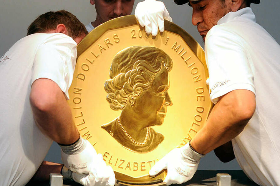 Mitarbeiter heben die 100 Kilo schwere Münze an ihren Platz. Das Bild zeigt ein Exemplar in Wien.
